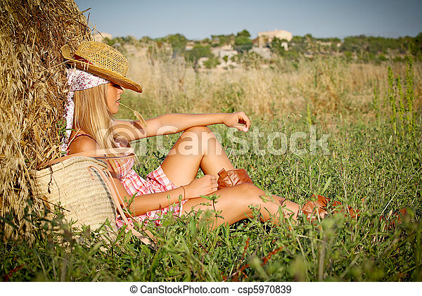 young woman relaxing in field outdoors in summer - csp5970839