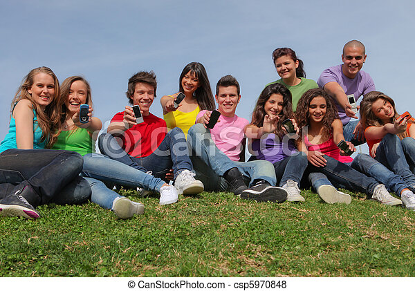 Group of mixed race showing cell phone or mobile telephones - csp5970848
