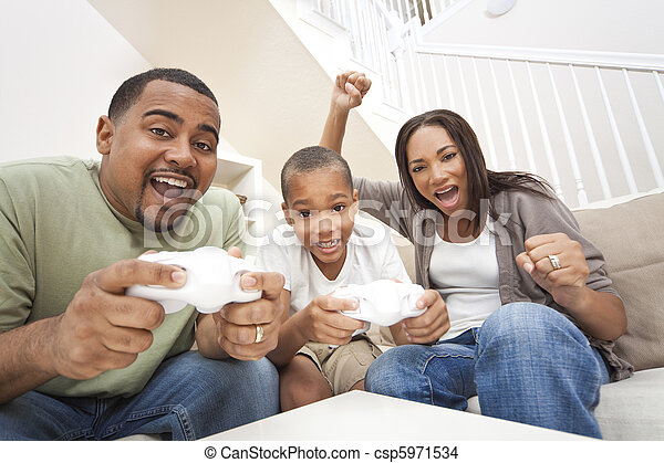 African American family, parents and son, having fun playing computer console games together, Father and son have the handset controllers and the mother is cheering the players. - csp5971534