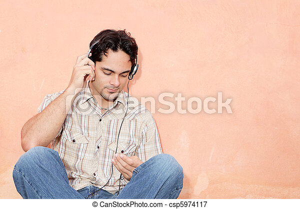man listening to music with earphones and personal stereo - csp5974117