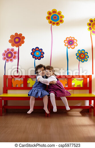 Two little girls smile and hug at school - csp5977523