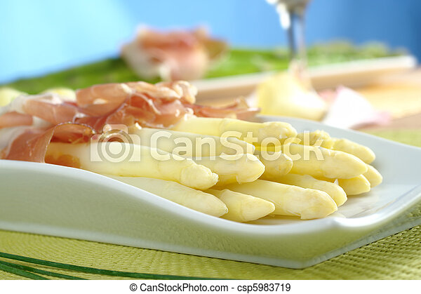 Fresh cooked white asparagus served with ham with white wine and green asparagus in the background (Selective Focus, Focus on the front of the asparagus on the left) - csp5983719