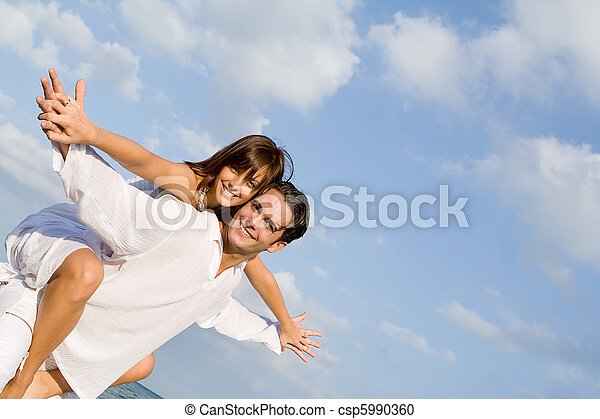 happy couple on holiday vacation or honeymoon piggyback fun - csp5990360