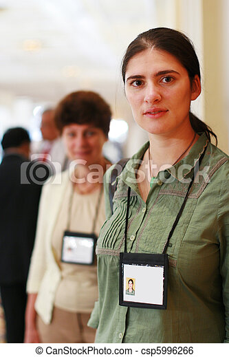 Two business women at trade show with name badges. - csp5996266