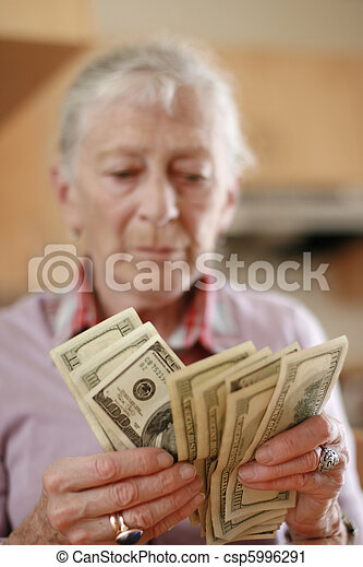 Senior woman counting savings money. Shallow DOF, focus on hands. - csp5996291