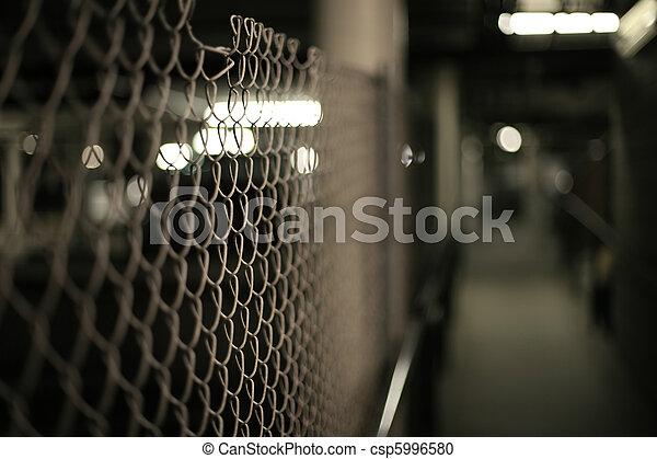 Mesh fence in an underground garage structure. Shallow DOF. - csp5996580