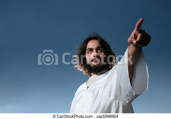 Man looking like Jesus pointing his finger, dramatic blue sky behind. - csp5996664