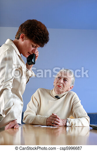 Elderly woman on appointment with social worker. Shallow DOF, focus on elderly lady. - csp5996687