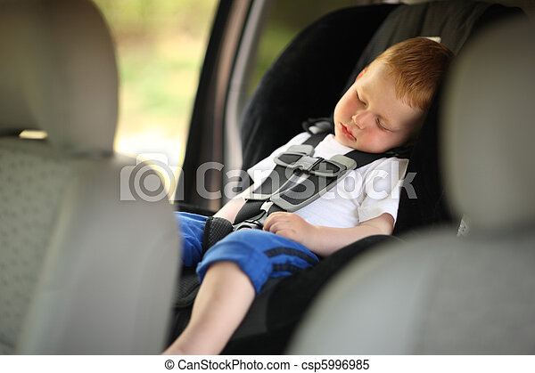 Boy sleeping in child car seat - csp5996985