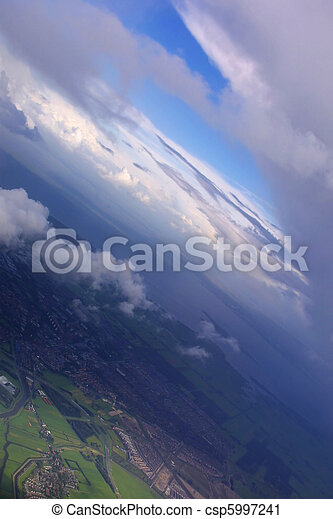 Aerial of earth view with dramatic clouds and blue sky - csp5997241