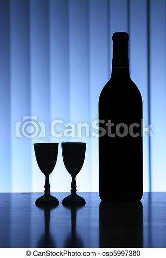 Wine bottle with two glasses, dramatic light, copy-space for text. - csp5997380
