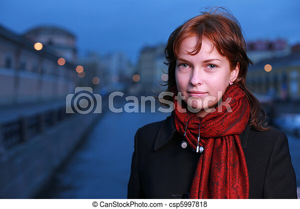 Portrait of a young redhead woman standing by a canal in St. Petersburg, Russia. - csp5997818