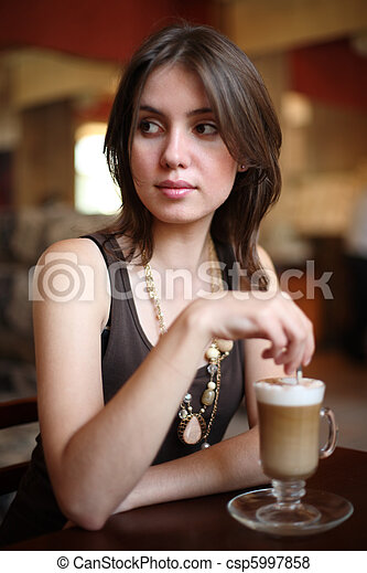 Beautiful young woman enjoying latte coffee in cafe. Shallow DOF. - csp5997858
