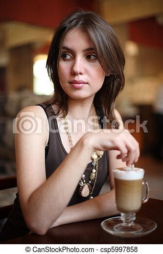 Beautiful young woman enjoying latte coffee in cafe. Shallow DOF. - csp5997858