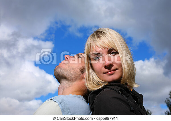 Man resting head on woman's shoulder, looking at the sky. - csp5997911