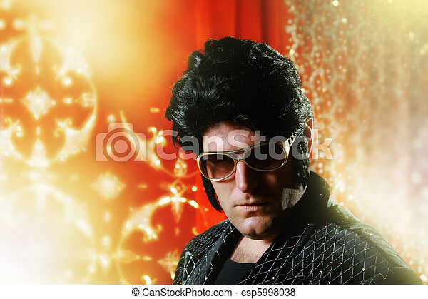 Elvis Presley impersonator over glowing background. - csp5998038