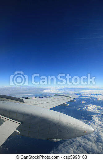 Airplane wing and blue sky. Lots of copy-space available. - csp5998163