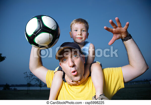 Dad and son playing football outdoors - csp5998225