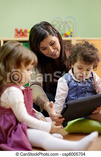 Teacher reading fairy tale to children at school - csp6005704
