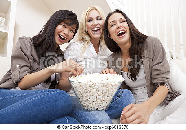 Three beautiful young women friends at home eating popcorn watching a movie together and laughing - csp6013570