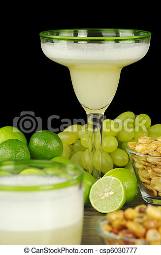 Pisco Sour, a Peruvian cocktail made of pisco, lime juice, sugar syrup and egg white. The cocktail is surrounded by grapes, limes, and Peruvian snacks, habas and canchas. (Selective Focus, Focus on th - csp6030777