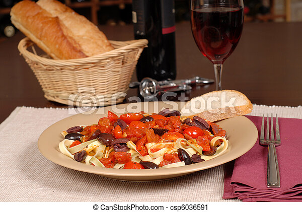 Plate of pasta puttanesca with wine and bread