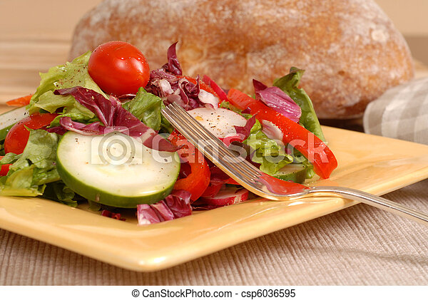 Side view of a crisp healthy salad on a yellow plate with rustic bread and a fork - csp6036595