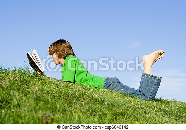 child reading book outdoors - csp6046142