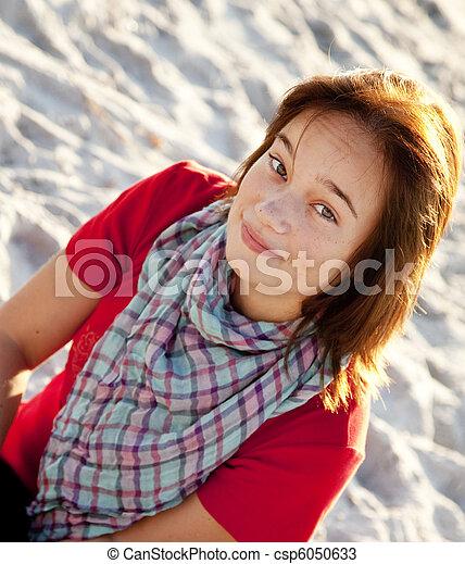 Beautiful brunet girl sitting at sand - csp6050633