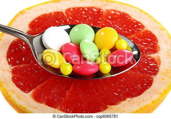 Vitamins on a slice of citrus. - csp6065781