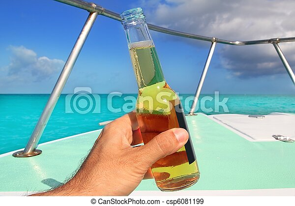 beer on hand Caribbean in boat bow turquoise sea - csp6081199
