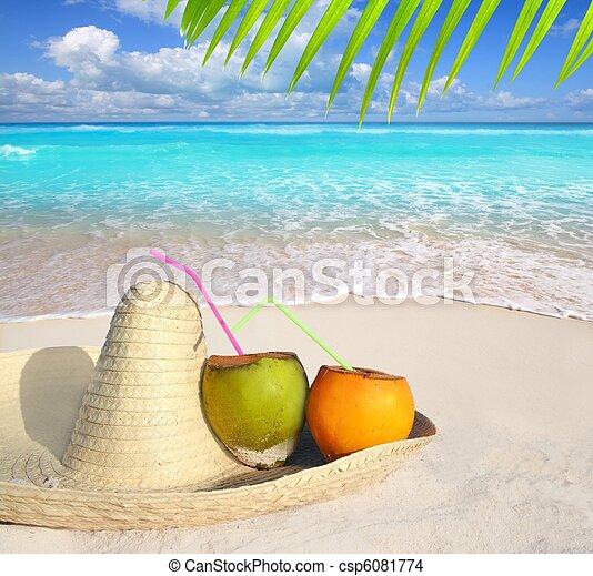 Coconuts in Caribbean beach on mexico sombrero hat - csp6081774