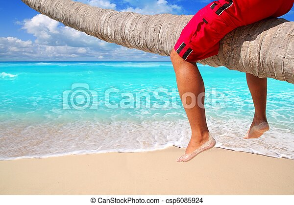 Caribbean inclined palm tree beach tourist legs - csp6085924