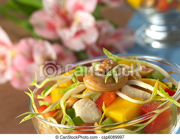 Fresh Asian salad with chicken, mango, cucumber, bean sprouts, red bell pepper and peanuts in glass bowl with inca lily in the back (Selective Focus, Focus on the cashew nut and the bean sprout on the - csp6089997