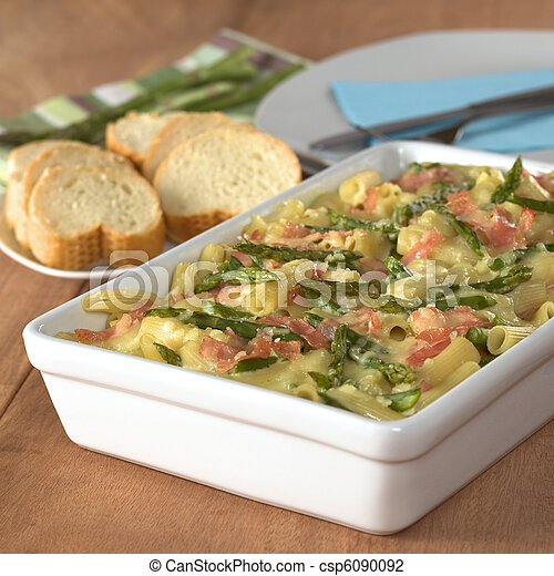 Casserole of green asparagus, ham and macaroni with baguette slices and plates in the back (Selective Focus, Focus in the middle of the dish) - csp6090092