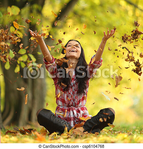 woman drop leaves in autumn park