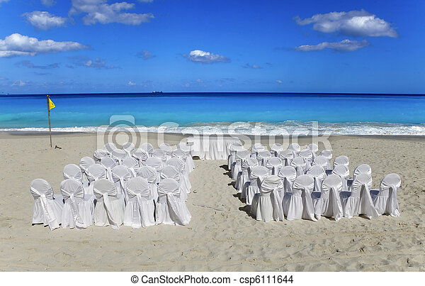 Wedding on tropical beach.  Chairs and tables in expectation of visitors. - csp6111644
