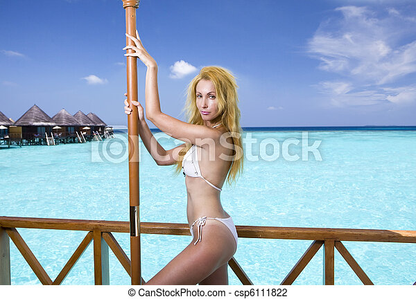 Young pretty woman in bathing suit  at villa on water, Maldives - csp6111822