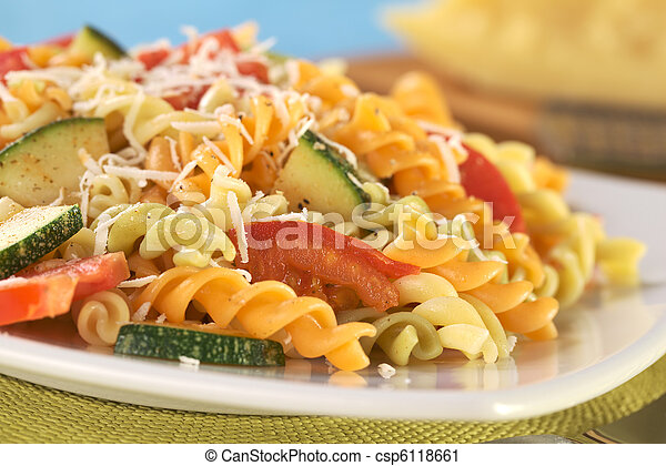 Colorful fusilli pasta with zucchini, tomato and grated cheese (Selective Focus, Focus on the tomato in front) - csp6118661