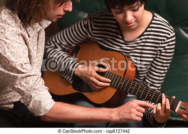 Young Musician Teaches Female Student To Play the Guitar - csp6127442
