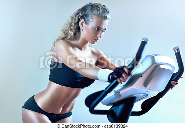 Young woman on exercise bicycle - csp6139324
