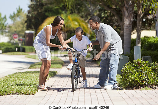 African American Family WIth Boy Riding Bike & Happy Parents - csp6140246
