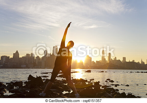 A woman runner stretching in a yoga position in front of the Manhattan skyline, New York City, United States of America, at early morning dawn sunrise - csp6151357