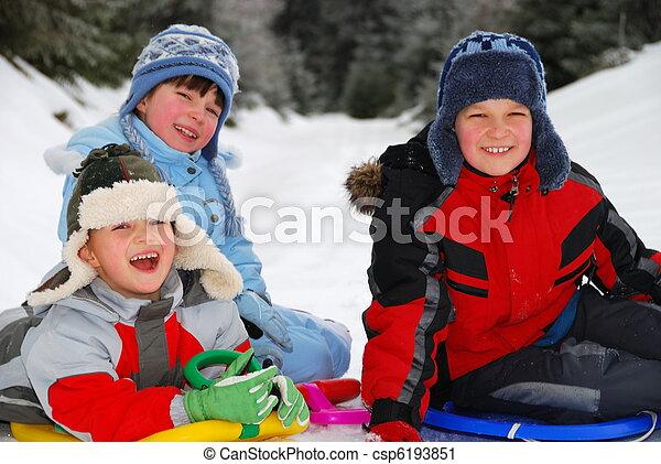 Winter portrait of three smiling children sitting on sledges on snow.