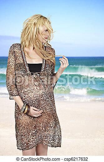 pregnant woman on windy beach - csp6217632