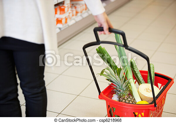 Woman pulling Shopping Basket in Grocery Store - csp6218968
