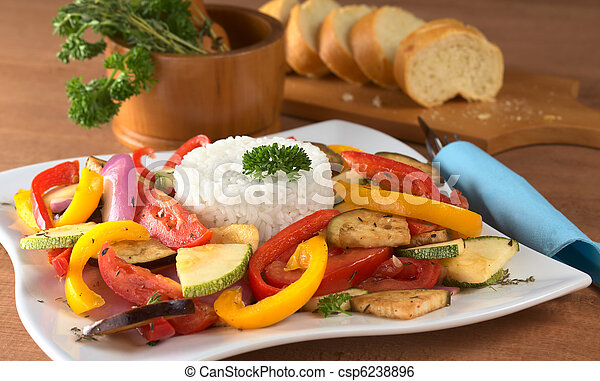 Ratatouille of zucchini, eggplant, tomato, bell pepper and onion with cooked rice and mortar with herbs and baguette in the back (Selective Focus, Focus on the front of the rice and the vegetable arou - csp6238896
