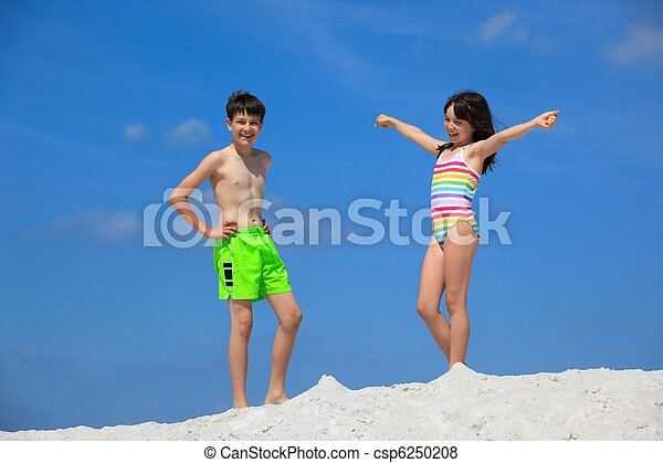 Kids in bathing suits on beach - csp6250208