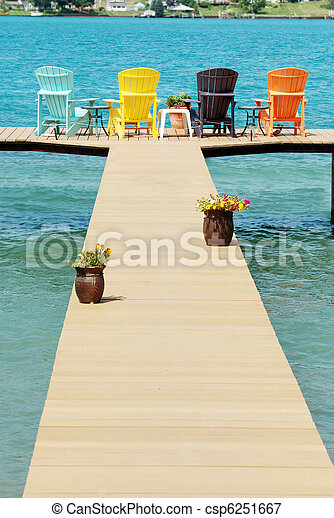 dock with colorful adirondack chair - csp6251667