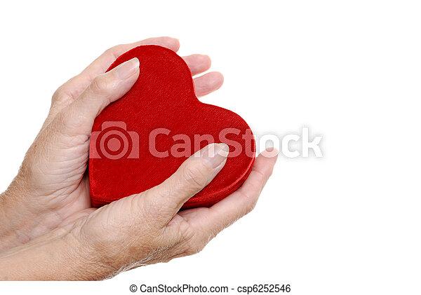 elderly woman hands holding a heart - csp6252546